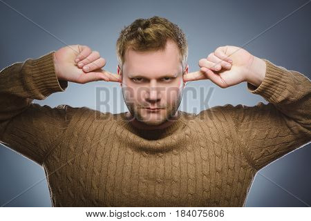 Closeup portrait of worried man covering his ears, observing. Hear nothing. Human emotions, facial expressions.