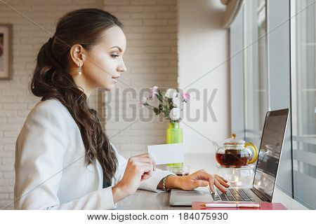 Elegant lady propose start cooperation without stop working. Dark-haired woman typing on laptop. Daylight illuminates table. Vase of flowers, kettle and cup with tea, diary, elegant pen and notebook.