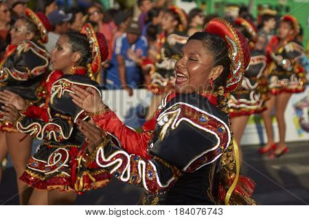 ARICA, CHILE - FEBRUARY 10, 2017: Female members of a Caporales dance group in ornate costumes performing at the annual Carnaval Andino con la Fuerza del Sol in Arica, Chile.
