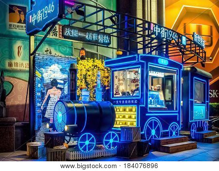 Shanghai, China - Nov 3, 2016: Night scene on Nanjing Road Pedestrian Street - outdoor store in style of locomotive decorated with neon lights selling ice cream and other dairy products. A busy tourist area.