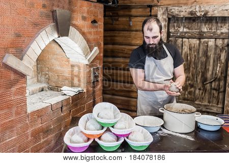 Men knead the dough for bread next to the wooden door and the rainforest.