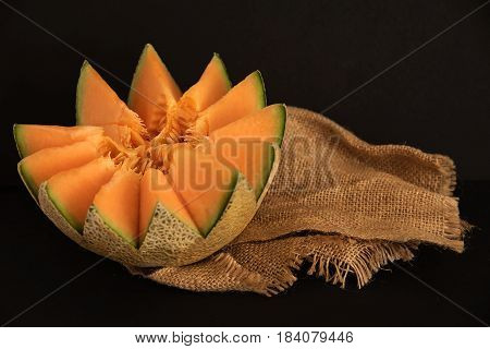 Juicy carving and half cut honeydew melon isolated on black background