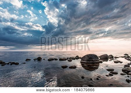 Colorful sky and stony beach at sunset lights.