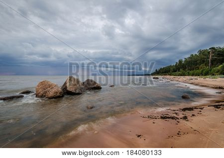 Seascape. Storm clouds gathering over the rocky beach.