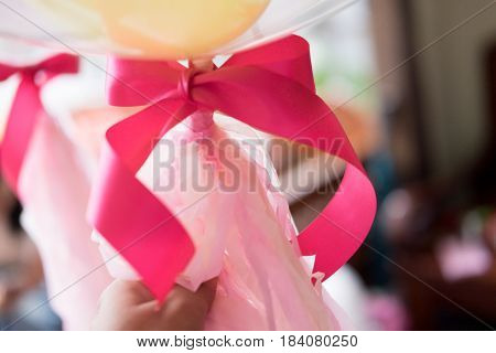 pink ribbon close up in bunch of balloons at party