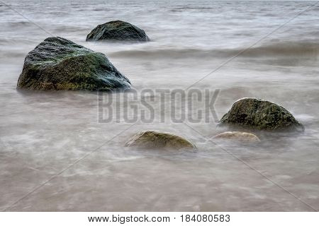 Marine waters surrounded by lone large stones.