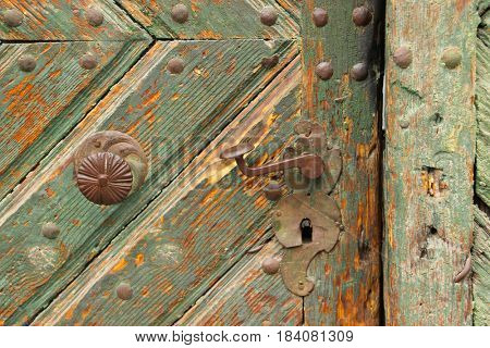 Vintage iron door handle on an old wood door. Close up detail