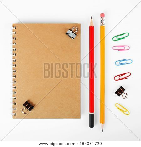 Stationery - Notebook binder clip paperclip and two graphite pencils on a white background.
