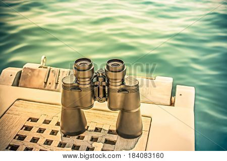 Binocular on boat ladder above water. Conceptual vintage background with copy space.
