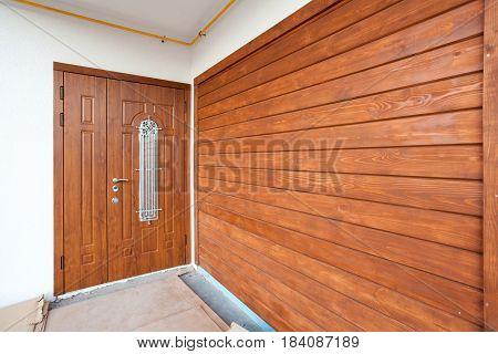 Modern entrance door with brown wooden panel