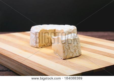 Cheese with white mold. Camembert or brie type on wood table. Healthy breakfast
