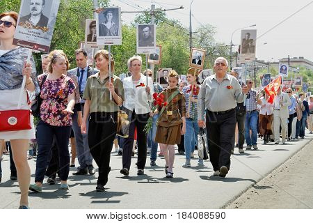 Volgograd Russia - May 09 2016: Participants of Immortal Regiment with portraits of their relatives walking along the street on Victory day in Volgograd