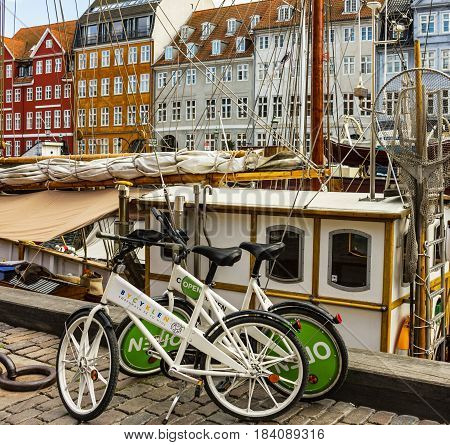 COPENHAGEN, DENMARK - APRIL 30, 2017: Bicycles on waterfront Nyhavn in the center of Copenhagen, Denmark. Nyhavn is historical district in Copenhagen. It is lined by brightly colored townhouses and restaurants.