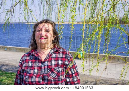 A portrait of a happy smiling woman on a background of river among willow twigs