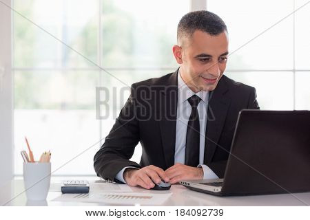 Happy Young Businessman Looking At Computer Screen