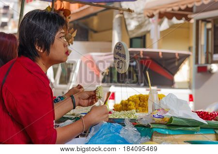 BANGKOK, Thailand - February 14, 2017 : Flower market name Pak Klong Talad in Bangkok. A portrait thai woman making traditional buddhist