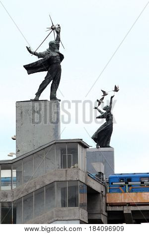 KIEV, UKRAINE - MAY 3, 2011: These pylons are subway stations that serve as pedestals for two monumental sculptures in the form of a woman with pigeons and a worker figure.