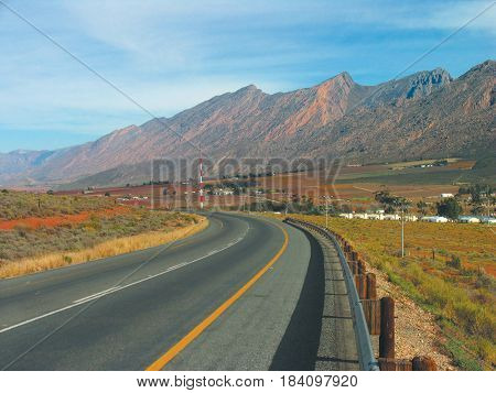 LANDSCAPE, FROM CAPE TOWN SOUTH AFRICA, ROAD AND VEGETATION IN FORE GROUND AND MOUNTAINS IN BACK GROUND 21bfe
