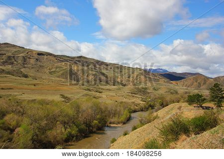 multi-level hills, mountains between which the river flows, the trees, the beautiful sky with white clouds