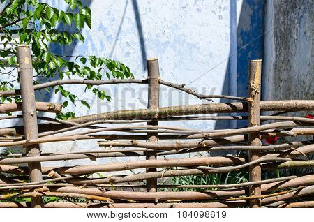 A braided wooden fence made of thin old branches in the countryside against the backdrop of an old house
