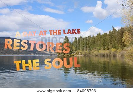 Conceptual inspiring image with scenic lake landscape. Calm water and reflections on water. Colorful text: A day at the lake restores the soul.