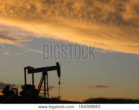 Lone pumpjack with a blue sky and  bright orange cloud