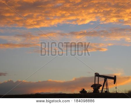 A single oil well beneath and orange sky