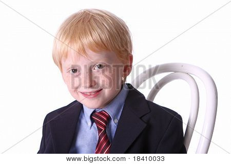 Dressed up boy sitting on chair on isolated background