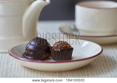 Chocolate petit four, cup and kettle of tea