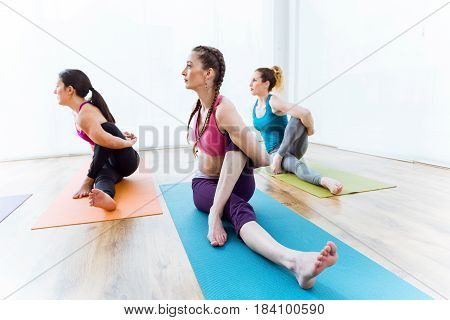 Portrait of group of people practicing yoga at home. Marichyasana pose.