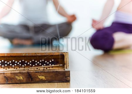 Close-up of incense stick behind couple doing yoga at home.