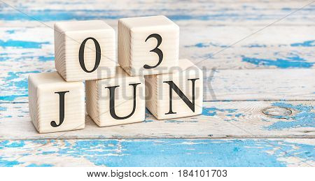 June 3rd. Wooden cubes with date of 3 June on old blue wooden background.