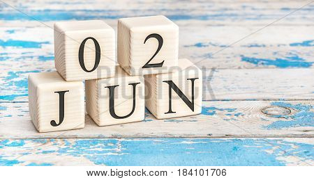 June 2nd. Wooden cubes with date of 2 June on old blue wooden background.