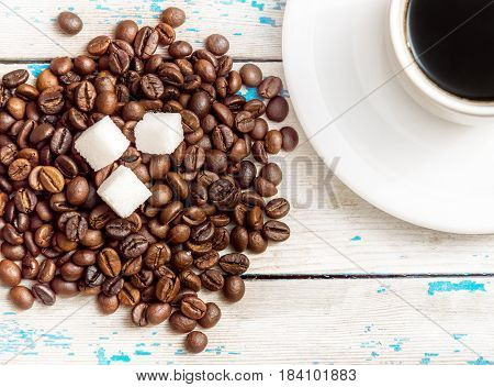 Heap of coffee beans with cubes of sugar and cup of coffee on wooden background.