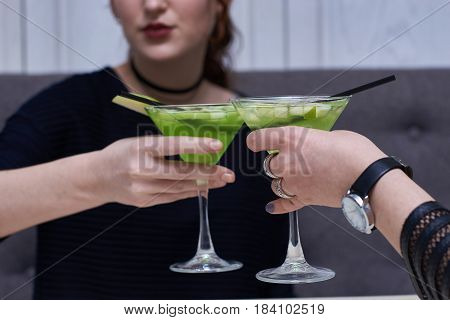 Two glasses of apple martini. Woman hands holding cocktails