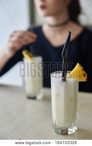 Two glasses of pina colada cocktail and pineapple slices on table in cafe. Young woman blurred at background
