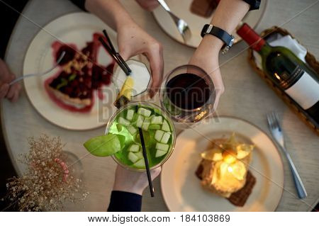 Girls party in cafe. Young woman drinking cocktails and wine and eating cakes. Female hands.