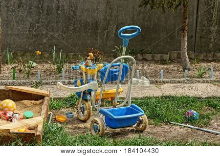 Children's tricycle next to the sandbox and toys