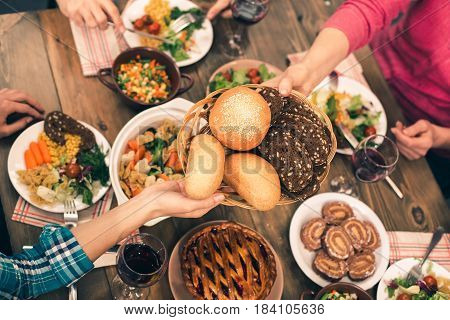 Family dinner. Beautiful family having meal. Tasty food on table. Happy family enjoying time together. Woman giving bread