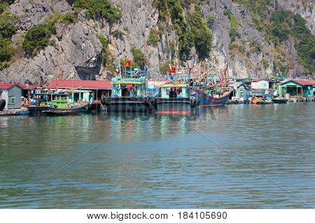 Floating fishing village with rock island in background, Ha Long bay, Vietnam.