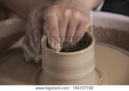 Close-up of the hands of a craftsworker ceramist molding a vase in his potter wheel.Ceramist workshop