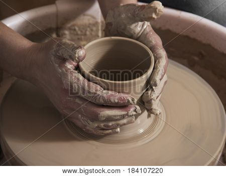 potter makes a pot of clay, working on the potter's wheel.Ceramist workout