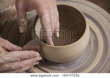 Close-up of the hands of a craftsworker ceramist molding a vase in his potter wheel.