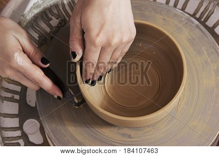 Close-up of the hands of a craftsman ceramist molding the clay in her potter wheel.Ceramist workshop