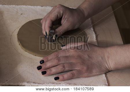 Ceramist using plants to print on a clay.Ceramist workshop