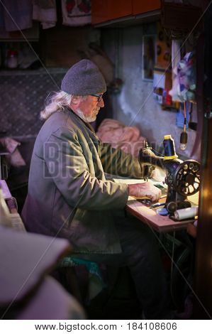 Senior Adult Man With Sewing Machine