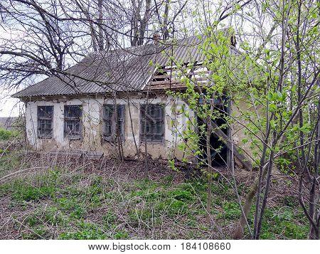 Abandoned farmhouse with broken door in the overgrown garden