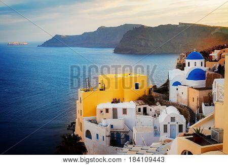 lanscape of Oia with blue church domes, volcano caldera and Aegan sea, beautiful details of Santorini island, Greecer, retro toned