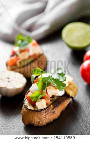 Tasty savory tomato Italian bruschetta, on slices of toasted baguette garnished with parsley, close up on a wooden black board