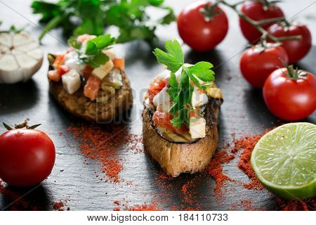 Tasty savory tomato Italian bruschetta, on slices of toasted baguette garnished with parsley, close up on a wooden black board. Horizontal
